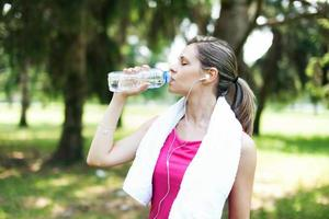 Active woman drinking water photo
