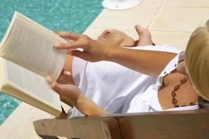 Woman reading a book by the pool.