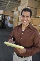 Mid-adult man stock-taking in warehouse photo