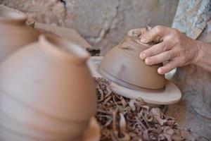 Moroccan artisan throws a clay pot on a potters wheel.