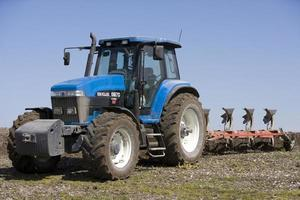 tractor y arado en campo foto