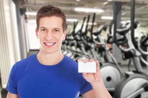 Hombre apto con tarjeta de visita en blanco foto