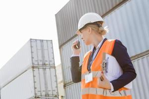Female engineer using walkie-talkie in shipping yard photo