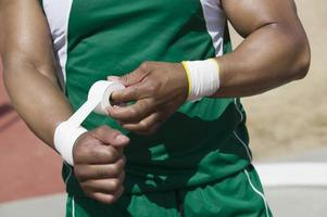 Male shot putter wrapping wrist tape, mid section photo