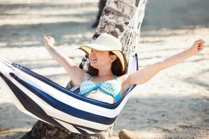 vrouw die zich uitstrekt in hangmat op het strand