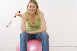 Young woman on exercise ball holding paint roller, smiling, port
