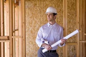 architect met blauwdrukken in veiligheidshelm in gedeeltelijk gebouwd huis