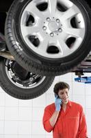 Male car mechanic using mobile phone