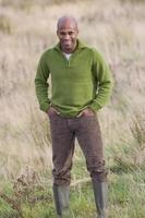 Hombre sonriente de pie en el campo con las manos en los bolsillos