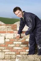 hombre pared de albañilería con llana foto