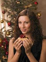 Mujer sosteniendo un regalo delante de un árbol de Navidad.