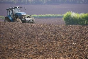 Tractor ploughing field photo