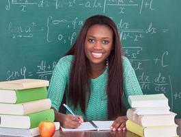 maestra segura escribiendo en el libro en el escritorio del aula foto