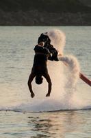 Flyboarder en silueta buceando verticalmente en aguas bravas foto