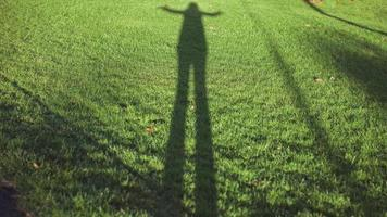 girl silhouette shadow on the grass photo