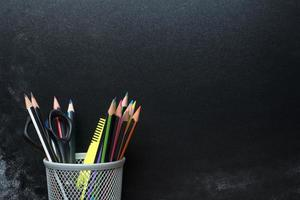 Pencils in cup  front of blackboard. photo
