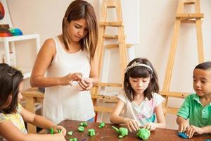 Art teacher during sculpting class photo