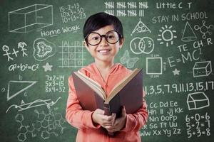 Adorable girl reads book near the blackboard