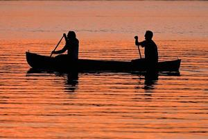 Couple Canoeing During Sunset photo