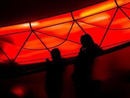 Fondo borroso oscuro de personas detrás del vidrio y luz de fondo roja foto