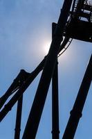 sun behind the roller coaster photo