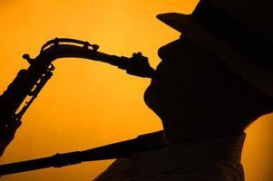 saxofón jugado en silueta fondo dorado foto