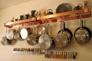 Close-up of metal pots and Pans hanging on the kitchen wall