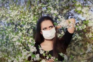 Chica alérgica con máscara de respirador en decoración floreciente primavera foto