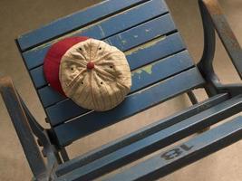 Close-up of old stadium seat with antique cap photo