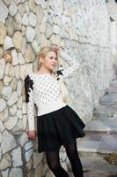 joven y guapa mujer cerca del muro de piedra