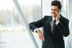 sonriente hombre de negocios hablando por teléfono móvil