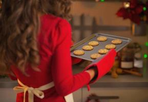 closeup on pan with christmas cookies in hand of housewife