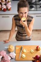 Happy woman biting into apple quarter in kitchen photo