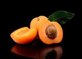 Three sliced apricots isolated on black photo