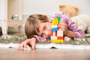 niño alegre jugando en la alfombra foto