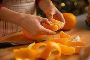 Primer plano de joven ama de casa dividiendo rodajas de naranja