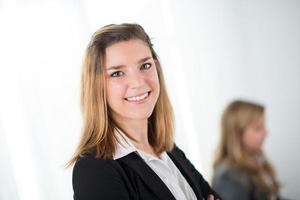 Cheerful young business woman standing up photo