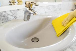 cleaning gray sink with cloth photo
