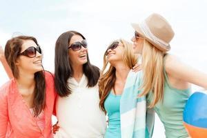 chicas sonrientes con pelota y toalla en la playa foto