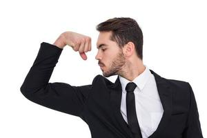 Cheerful businessman tensing arm muscle