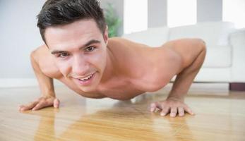 Cheerful handsome man doing push ups