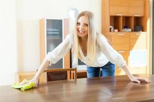 mujer alegre, limpieza de mesa en casa