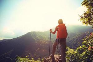 juichende vrouwenwandelaar die aan bergpiek beklimt
