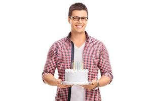 Cheerful young guy holding a birthday cake photo