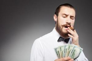 Cheerful young bearded businessman is carrying money