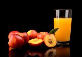 Close-up shot sliced orange nectarines with juice and leaf photo