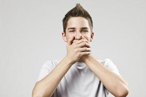 Cheerful teenage boy covering his mouth photo
