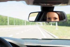 Cheerful young woman is driving her car photo