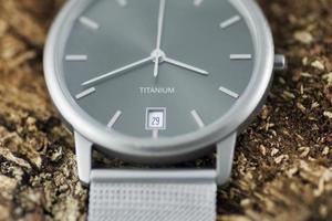 reloj de titanio en corteza de árbol