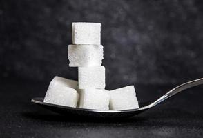 cloose up white sugar cubes in metal spoon photo